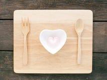 陶瓷心形的碗和桃红色蛋白软糖和木匙子有叉子的在木板 免版税库存图片