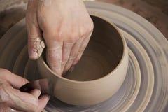 陶瓷技师的手的特写镜头工作在他的横式转盘的 免版税库存图片