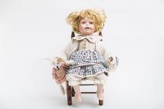 陶瓷有大蓝眼睛和卷曲金发的瓷手工制造玩偶 免版税库存照片