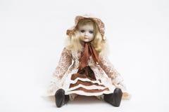 陶瓷有纺织品帽子和棕色礼服的瓷手工制造白肤金发的玩偶 免版税图库摄影