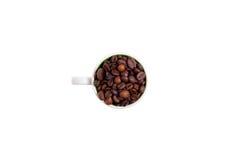 陶瓷杯子用咖啡豆,顶视图填装了 免版税库存图片