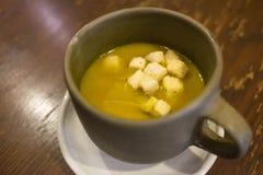 陶瓷杯热的南瓜汤用在上面的油煎方型小面包片 免版税库存图片