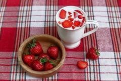 陶瓷杯酸奶,红色新鲜的草莓在检查桌布的木板材 早餐有机健康鲜美食物 免版税库存图片