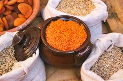 陶瓷泥罐用红色小扁豆和大袋豆类和五谷在食物市场上站立 免版税库存照片