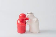 陶瓷玩偶红色和白色婚戒顶上的感觉拥抱 库存图片