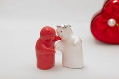 陶瓷玩偶红色和白色婚戒顶上的感觉拥抱 图库摄影