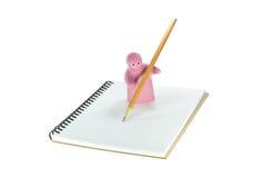 陶瓷玩具在笔记薄写着那 免版税库存图片