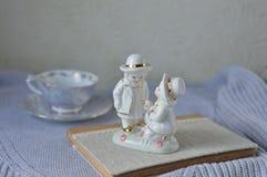 陶瓷的茶杯和的小雕象 免版税库存图片