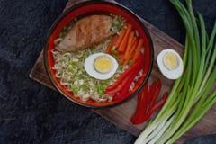 陶瓷碗传统亚洲拉面汤用面条,春天葱,鸡,切了鸡蛋,供食与木筷子 免版税库存图片