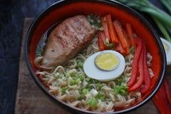 陶瓷碗传统亚洲拉面汤用面条,春天葱,鸡,切了鸡蛋,供食与木筷子 免版税图库摄影