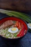 陶瓷碗传统亚洲拉面汤用面条,春天葱,鸡,切了鸡蛋,供食与木筷子 图库摄影