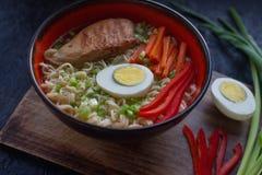 陶瓷碗传统亚洲拉面汤用面条,春天葱,鸡,切了鸡蛋,供食与木筷子 库存照片