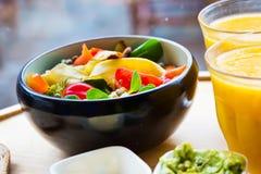 黑陶瓷碗用健康五颜六色的有机新鲜的沙拉和两块汁液玻璃 免版税图库摄影