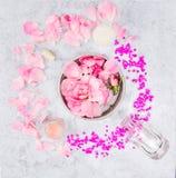 陶瓷碗用rpnk玫瑰和水,瓶子在灰色大理石桌上的奶油和玻璃瓶 免版税库存照片