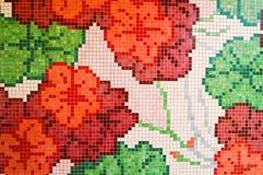 陶瓷马赛克的纹理是明亮的,红色,桃红色,与绿色词根,花形式的许多元素 库存图片