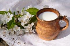 陶瓷水罐用在一个地道亚麻制桌布和开花的樱桃分支的新鲜的新的牛奶 Sprng早晨静物画 库存照片