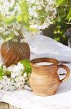 陶瓷水罐用在一个地道亚麻制桌布和开花的樱桃分支的新鲜的新的牛奶 Sprng早晨静物画 免版税图库摄影