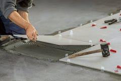 陶瓷ceranic纹理瓦片 安置陶瓷墙壁瓦片的铺磁砖工在位置  库存照片