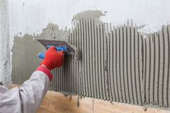 陶瓷ceranic纹理瓦片 涂黏着性材料的Tilerman手 免版税库存图片