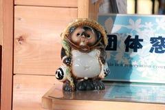 陶瓷Tanuki雕象它是动物雕塑或日本狸在票销售逆在Kameoka Torokko驻地 免版税库存图片
