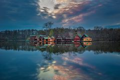陶陶,匈牙利-在木钓鱼的村庄的美好的日落在湖的对在11月的Derito Derito一个小海岛上 库存图片
