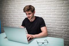 随便使用膝上型计算机的穿戴的年轻商人,当坐时 图库摄影