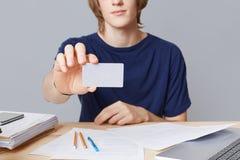 随便穿戴的年轻男性enterpreneur的播种的图象拿着与blnk拷贝空间的卡片,坐工作表, sorrounded与 免版税库存图片