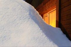随风飘飞的雪和黄色窗口 库存照片