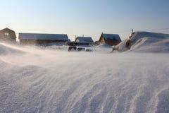 随风飘飞的雪的积雪的村庄房子 免版税库存照片