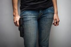 隐瞒武器的女孩官员 免版税库存图片
