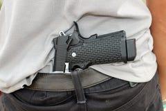 隐瞒他的在他的后的匪徒枪  免版税库存照片