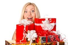 隐藏在圣诞节礼物之后的俏丽的女孩 免版税库存图片
