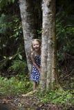隐藏在结构树之间的女孩 免版税图库摄影