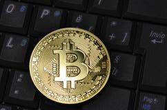 隐藏在键盘的货币物理金bitcoin特写镜头  免版税库存照片