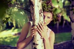 隐藏的新可爱的妇女在森林 免版税库存图片