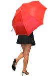 隐藏红色伞的美丽的女孩下 免版税图库摄影