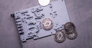 隐藏货币:在一张灰色电路板的几枚Dashcoin硬币 免版税库存图片