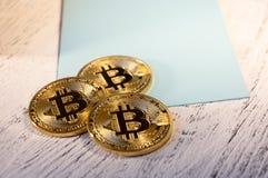 隐藏货币Bitcoin几枚硬币在一张蓝色明信片说谎 库存图片