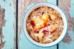 隔夜早餐燕麦用桃子和椰子在蓝色木头 免版税库存图片