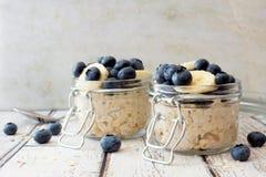 隔夜燕麦用蓝莓和香蕉在白色木背景 免版税库存图片