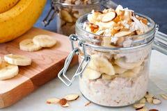 隔夜燕麦用香蕉和坚果在玻璃装于罐中的瓶子 库存照片