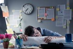 隔夜睡觉在办公室的商人 免版税库存照片
