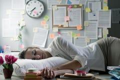 隔夜睡觉在办公室的妇女 免版税库存图片