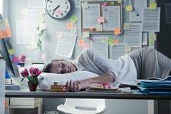 隔夜睡觉在办公室的妇女 库存照片