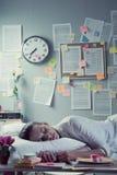 隔夜睡觉在办公室的妇女 免版税库存照片