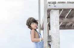 隔绝在白色,上升在木码头顶部的时髦的俏丽的女孩 免版税库存照片