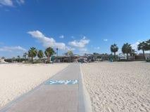 障碍在卓美亚奢华酒店集团海滩迪拜阿拉伯联合酋长国的海滩通入 一个沙滩的风景视图与残疾通入和餐馆咖啡馆的 库存图片