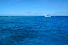障碍小船极大的海洋礁石 免版税库存照片