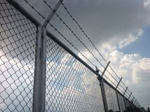 障碍或倒钩导线和白色云彩 免版税库存照片