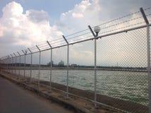 障碍或倒钩导线和绿色水 库存图片